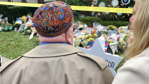 Judah Samet stands at the synogague's makeshift grave markings for the 11 killed now surrounded by police tape, mourners flowers.