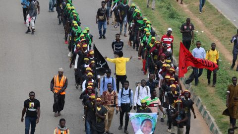 Members of the Islamic Movement of Nigeria (IMN) wave flags and chant slogans as they take part in a demonstration in Abuja on October 29 to protest the imprisonment of a Shiite cleric.