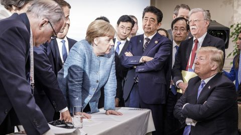 In this photo provided by the German Government Press Office, Merkel talks with Trump as they are surrounded by other leaders at the G7 summit in June 2018. According to two senior diplomatic sources, <a href=