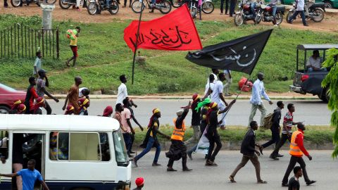 Members of Islamic Movement of Nigeria (IMN) wave flags and chant slogans as they take part in a demonstration to protest against the imprisonnement of a Shiite, in Abuja, on October 29, 2018. - The army and police confronted members of the Islamic Movement of Nigeria (IMN), the group's spokesman Ibrahim Musa told AFP, amid reports of casualties. Rights groups have accused Nigeria's military of killing more than 300 IMN supporters and burying them in mass graves during the 2015 confrontation, a charge the military strongly denies. (Photo by Sodiq ADELAKUN / AFP)        (Photo credit should read SODIQ ADELAKUN/AFP/Getty Images)