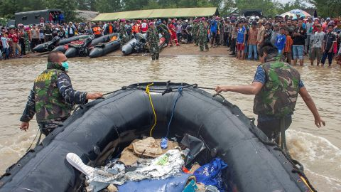 Soldiers drag ashore an inflatable raft containing debris from the plane.