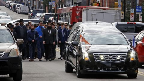 Mourners walk behind the hearse carrying the casket of Dr. Jerry Rabinowitz following a funeral service at the Jewish Community Center in the Squirrel Hill section of Pittsburgh, Tuesday Oct. 30, 2018. Rabinowitz was one of 11 people killed while worshipping at the Tree of Life Synagogue on Saturday Oct. 27, 2018. (AP Photo/Gene J. Puskar)