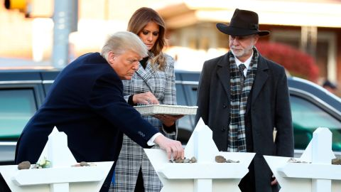 President Donald Trump and first lady Melania Trump put down stones from the White House at a memorial outside for those killed at the Pittsburgh's Tree of Life Synagogue in Pittsburgh, Tuesday, October 30, 2018, as Tree of Life Rabbi Jeffrey Myers watches.