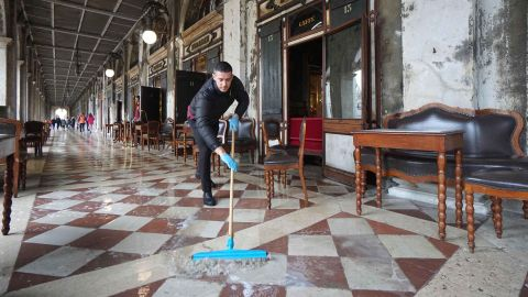 A man brushes away floodwater outside the historic Caffe Florian in St. Mark's Square on Tuesday.