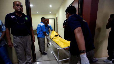 Officials transport a body bag in Jakarta.
