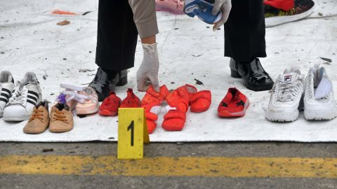 A police officer arranges shoes recovered during search operations.