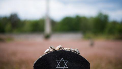 Pebble stones lie on a memorial stone at Bergen Belsen.
