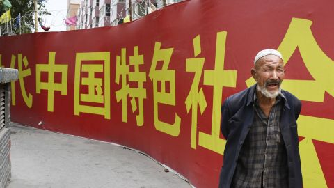 Photo taken on July 2, 2018, shows a man walking past a wall bearing a China Communist Party slogan in Kashgar.