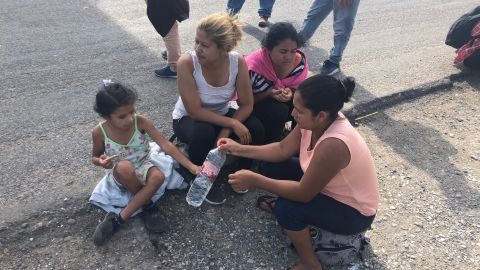 A group of women, including a mother and daughter, rest on the side of the road and share water en route to Juchitán, Oaxaca.