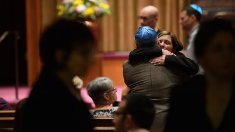 People of faith greet each other at Temple Sinai before Friday evening Shabbat services.