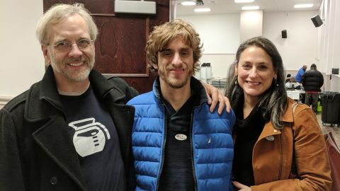 """Nathaniel Batchelder proudly wears an """"I Voted"""" sticker after casting an early ballot alongside father Ned Batchelder and mother Susan Senator."""