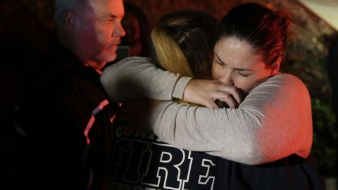 A woman who fled from the shooting gets hugs from relatives in Thousand Oaks.