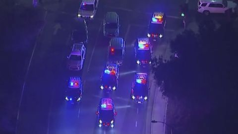 Police vehicles block an intersection near the shooting in an image from aerial video.