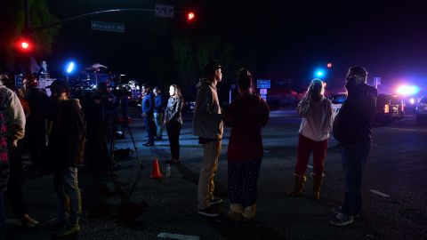 People stand and watch as the scene unfurls from the intersection of US 101 freeway and the Moorpark Rad exit as police vehicles close off the area outside a country music bar and dance hall in Thousand Oaks, west of Los Angeles, where a gunman opened fire late November 7, 2018, killing at least 12 people, US police said. (Photo by Frederic J. Brown/AFP)        (Photo credit should read FREDERIC J. BROWN/AFP/Getty Images)