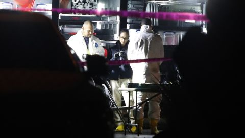 Investigators in hazmat outfits work out of the command center at the shooting scene.
