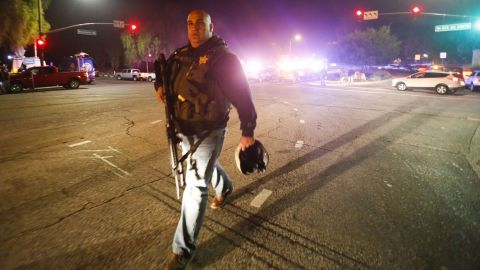 Law enforcement officers guard the road leading to the Borderline Bar and Grill.