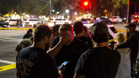 People stand in a parking lot along South Moorpark Road in Thousand Oaks in the aftermath of the shooting.