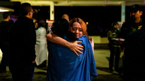 THOUSAND OAKS, CA - NOVEMBER 08:  Two people embrace each other others stand in a gas station parking lot along South Moorpark Road in the aftermath of a mass shooting at Borderline Bar & Grill, on Thursday, Nov. 8, 2018 in Thousand Oaks, California. The gunman burst into the bar around 11:20 p.m., cloaked in all black as he threw smoke bombs and began shooting at targets as young as 18 inside the Borderline Bar & Grill, authorities and witnesses said. (Photo by Kent Nishimura / Los Angeles Times via Getty Images)