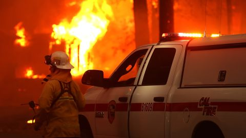 A firefighter monitors a burning home as the Camp Fire moves through Paradise, California, on November 8, 2018.