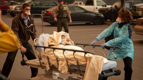 Patients are evacuated from Paradise's Feather River Hospital as it burns on Thursday, November 8.