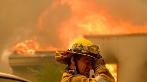 A firefighter keeps watch as a wildfire burns a home in Malibu, California. (AP Photo/Ringo H.W. Chiu)