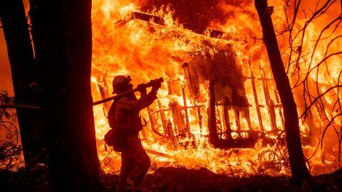 Firefighter Jose Corona sprays water as flames consume a house in Magalia, California.