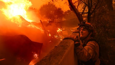 Malibu Mayor Rick Mullen, who is also a firefighter, surveys a house engulfed in flames on Friday, November 9.