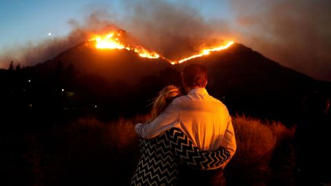 Roger Bloxberg and his wife, Anne, hug on Friday, November 9, as they watch a wildfire on a Los Angeles hilltop.