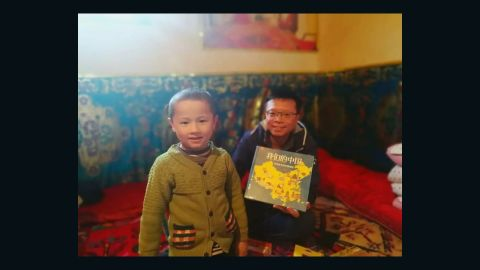 """A civilian worker presents a Uyghur child whom he has been assigned to treat as his """"relative"""" with a picture book titled Our China, in an undated photo from Xinjiang's Chinese Communist Youth League."""