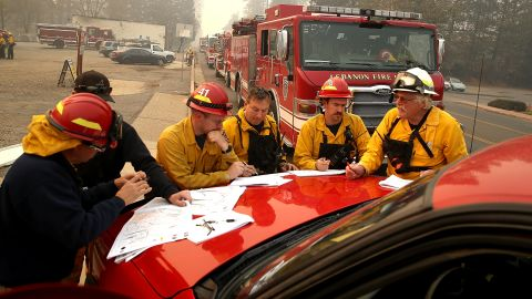 Firefighters hold a morning meeting as they battle the Camp Fire on Saturday in Paradise.