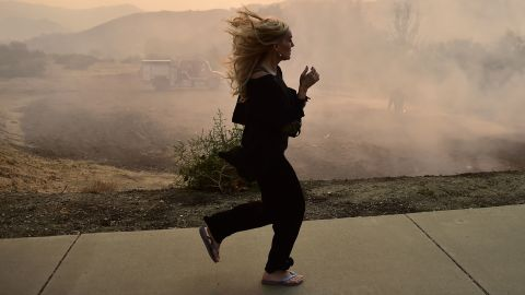A woman runs in Calabasas as firefighters work to control a flare-up from the Woolsey Fire on November 10.