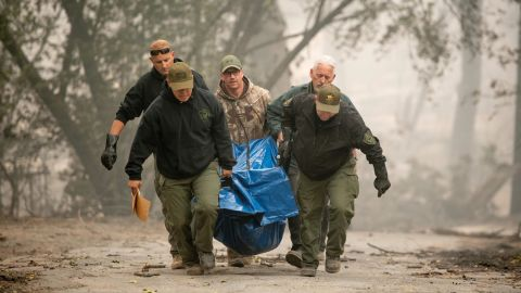 Yuba County Sheriff officers carry a body away from a burned residence in Paradise, California, on November 10, 2018. - Firefighters in California on November 10 battled raging blazes at both ends of the state that have left at least nine people dead and thousands of homes destroyed, but there was little hope of containing the flames anytime soon. So far, all nine fatalities were reported in the town of Paradise, in Butte County, where more than 6,700 buildings, most of them residences, have been consumed by the late-season inferno, which is now California's most destructive fire on record. (Photo by Josh Edelson / AFP)        (Photo credit should read JOSH EDELSON/AFP/Getty Images)