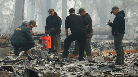 Yuba and Butte County sherriff's deputies sift through a destroyed home to collect the human remains of a victim of the Camp Fire on November 10 in Paradise.