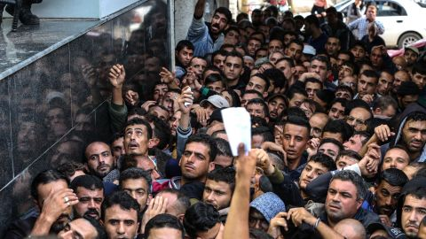 Palestinians gather to receive the cash which was brought into Gaza through Israel on Thursday by Qatar's Envoy to Gaza.