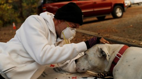 Evacuee Brian Etter and his dog Tone, who escaped the Camp Fire on foot, rest in the parking lot of a Chico church on November 11.