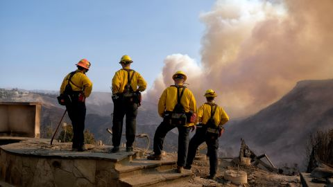 Culver City firefighters watch the Woolsey Fire from a burned home in Los Angeles.