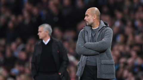 Man City's Pep Guardiola looks on in front of rival Jose Mourinho of Manchester United.