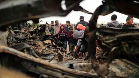 People gather Monday around a vehicle destroyed in an Israeli air strike in Gaza.
