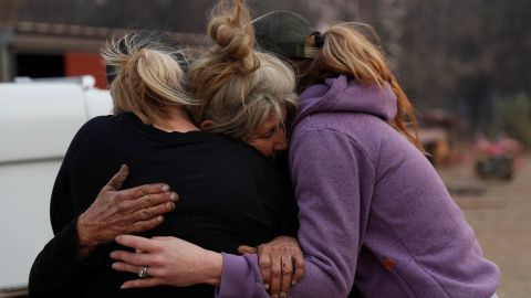 Cathy Fallon, who stayed behind in Paradise to tend to her horses during the Camp Fire, embraces Shawna De Long, left, and April Smith, right, who brought supplies for the horses.