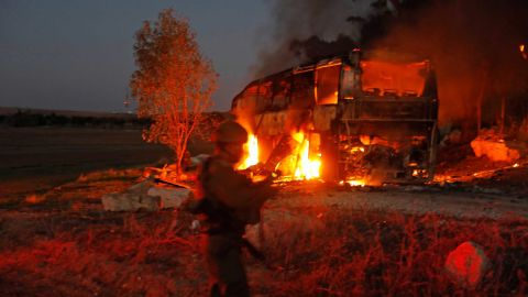 Israeli security forces and firefighters gather near the bus hit by fire from Gaza.