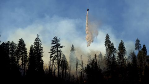 A helicopter drops water while battling the Camp Fire near Pulga on November 11.