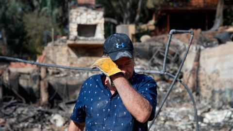 Roger Kelton wipes away tears on November 13 while searching through the remains of his mother-in-law's home in Agoura Hills. It was destroyed by the Woolsey Fire.