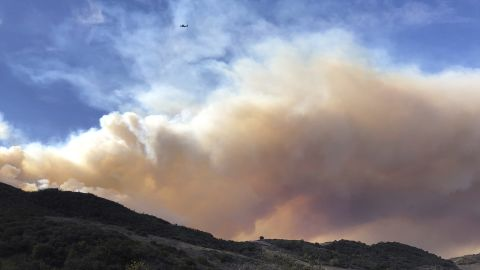 An airplane flies over a large wildfire plume from a recent flareup of the Woolsey Fire near Lake Sherwood, Calif., Tuesday, Nov. 13, 2018. Forecasters had warned of continuing fire danger in Southern California due to persistent Santa Ana winds, the withering, dry gusts that sweep out of the interior toward the coast, pushing back moist ocean breezes.  (AP Photo/Amanda Myers)
