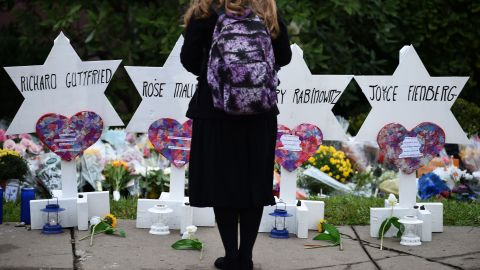 """TOPSHOT - A woman stands at a memorial outside the Tree of Life synagogue after a shooting there left 11 people dead in the Squirrel Hill neighborhood of Pittsburgh on October 27. - Mourners held an emotional vigil Sunday for victims of a fatal shooting at a Pittsburgh synagogue, an assault that saw a gunman who said he """"wanted all Jews to die"""" open fire on a mostly elderly group. Americans had earlier learned the identities of the 11 people killed in the brutal assault at the Tree of Life synagogue, including 97-year-old Rose Mallinger and couple Sylvan and Bernice Simon, both in their 80s.Nine of the victims were 65 or older. (Photo by Brendan SMIALOWSKI / AFP)        (Photo credit should read BRENDAN SMIALOWSKI/AFP/Getty Images)"""