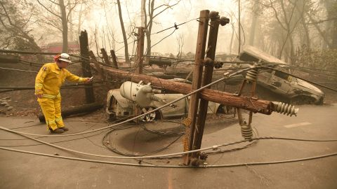 TOPSHOT - CalFire firefighter Scott Wit surveys burnt out vehicles near a fallen power line on the side of the road after the Camp fire tore through the area in Paradise, California on November 10, 2018. - Firefighters in California on November 10 battled raging blazes at both ends of the state that have left at least nine people dead and thousands of homes destroyed, but there was little hope of containing the flames anytime soon. So far, all nine fatalities were reported in the town of Paradise, in Butte County, where more than 6,700 buildings, most of them residences, have been consumed by the late-season inferno, which is now California's most destructive fire on record. (Photo by Josh Edelson / AFP) / The erroneous mention appearing in the metadata of this photo by Josh Edelson has been modified in AFP systems in the following manner: [CalFire firefighter Scott Wit] instead of [Retired CalFire firefighter Scott Wit]. Please immediately remove the erroneous mention from all your online services and delete it from your servers. If you have been authorized by AFP to distribute it to third parties, please ensure that the same actions are carried out by them. Failure to promptly comply with these instructions will entail liability on your part for any continued or post notification usage. Therefore we thank you very much for all your attention and prompt action. We are sorry for the inconvenience this notification may cause and remain at your disposal for any further information you may require.        (Photo credit should read JOSH EDELSON/AFP/Getty Images)