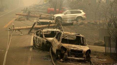 PARADISE, CA - NOVEMBER 10:  Power lines rest on cars that were burned by the Camp Fire on November 10, 2018 in Paradise, California. Fueled by high winds and low humidity, the rapidly spreading Camp Fire ripped through the town of Paradise and has quickly charred 100,000 acres and has destroyed over 6,700 homes and businesses in a matter of hours. The fire is currently at 20 percent containment.  (Photo by Justin Sullivan/Getty Images)