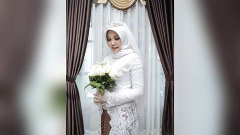 Intan Syari poses for a wedding photo alone, fulfilling her fiancé's final wish for her to do the shoot if he ever failed to return.