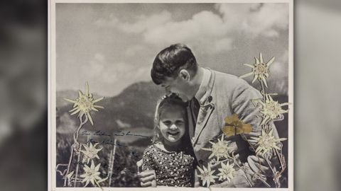 The photograph shows Hitler embracing Rosa Bernile Nienau, then about five or six, and is embellished with flowers which were placed by the young girl, Alexander Historical Auctions said.
