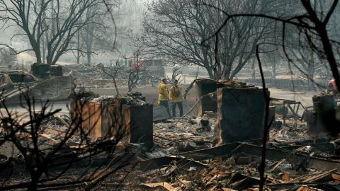 Firefighters search for human remains in a trailer park destroyed in the Camp Fire, Friday, Nov. 16, 2018, in Paradise, Calif. (AP Photo/John Locher)