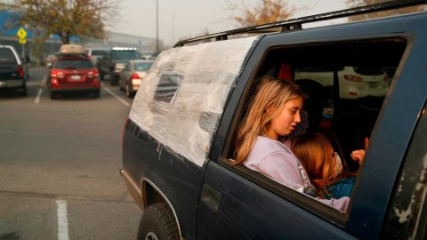 Dakota Keltner, right, rests on Havyn Cargill-Morris on November 16 in a truck at a makeshift encampment outside a Walmart store in Chico, California. The camp became a temporary respite for people displaced by the Camp Fire.